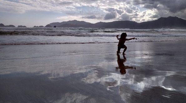 Anak asyik main di pantai pulau merah